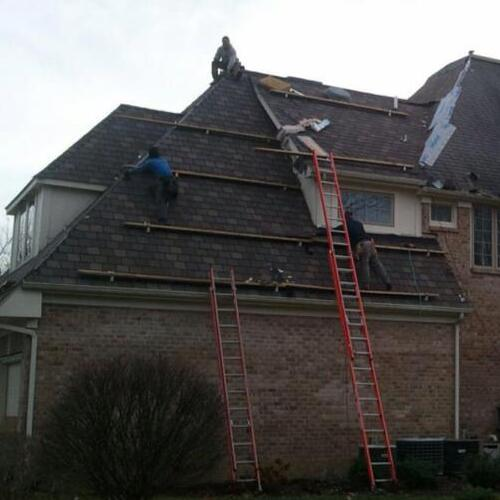 Roofers Work on an Asphalt Shingle Roof.