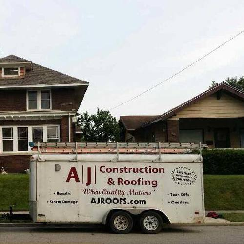 An AJ Construction & Roofing Trailer Outside a Home.